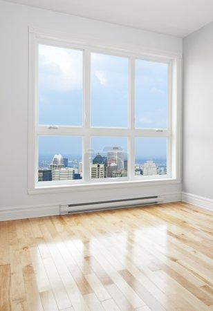 Photo pour Gratte-ciel de ville vue à travers la grande fenêtre d'une chambre vide. - image libre de droit