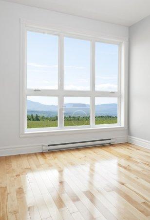 Photo pour Paysage d'été vu à travers la grande fenêtre d'une chambre vide. - image libre de droit