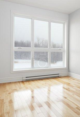 Photo pour Paysage d'hiver à travers la grande fenêtre d'une chambre vide. - image libre de droit