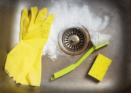 Photo pour Produits de nettoyage et des gants de caoutchouc dans un évier de cuisine sale. - image libre de droit