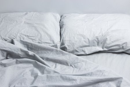 Photo for Messy bed with two pillows, gray bed linen. - Royalty Free Image