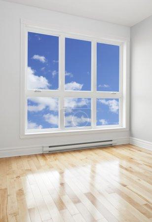 Photo pour Bleu ciel vu à travers la grande fenêtre d'une chambre vide. - image libre de droit