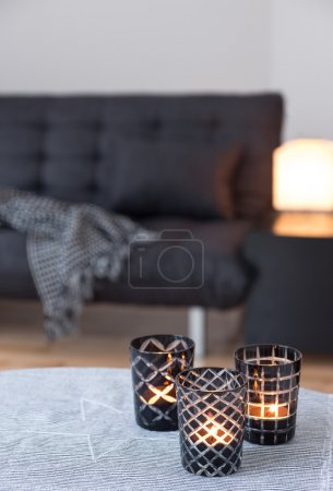 Photo pour Thé-lumières dans le porte-bougies en verre décoration salle de séjour avec canapé gris. - image libre de droit