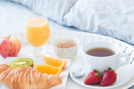 Photo pour Gros plan du plateau avec le délicieux petit déjeuner sur un lit. - image libre de droit