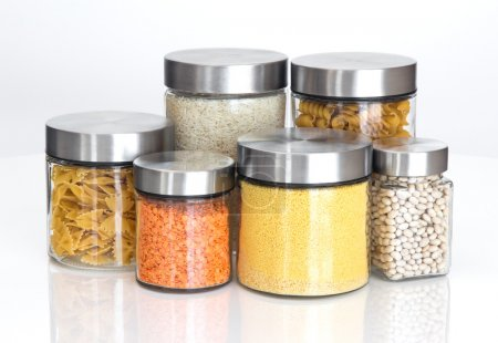 Food ingredients in glass jars, on white background