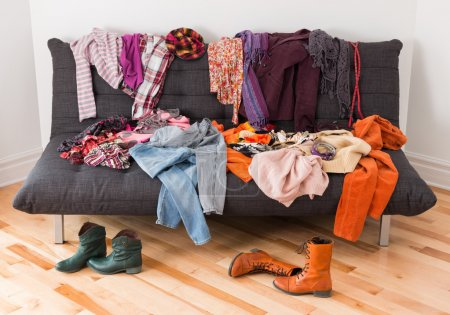Photo for What to wear? Messy colorful clothing on a sofa. - Royalty Free Image