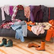 What to wear? Messy colorful clothing on a sofa....