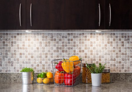 Photo pour Légumes, fruits et herbes dans une cuisine contemporaine avec un éclairage confortable. - image libre de droit
