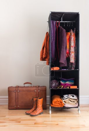 Photo for Mobile wardrobe with orange and purple clothing, and leather suitcase. - Royalty Free Image