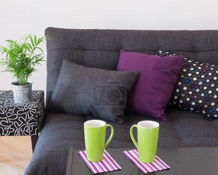 Photo pour Canapé décoré avec des coussins lumineux, plante verte et grandes tasses sur une table. - image libre de droit