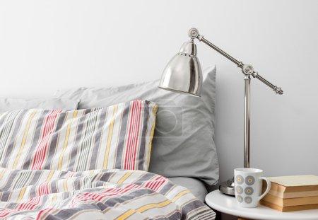 Photo pour Lampe et des livres sur un guéridon près de lit avec des draps colorés. - image libre de droit