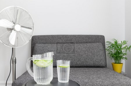 Photo for Electric fan near armchair, and some water to cool down. - Royalty Free Image