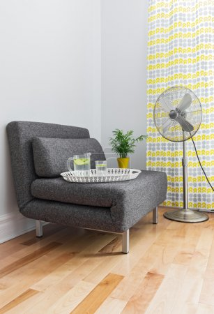 Photo for Armchair and electric fan in a contemporary living room. - Royalty Free Image