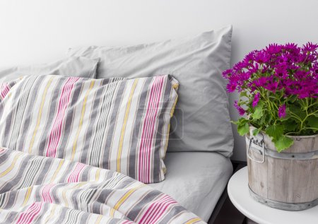 Photo for Modern bedroom decorated with bright purple flowers. Fresh design. - Royalty Free Image