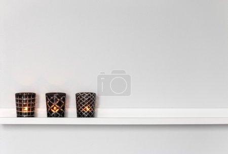 Photo pour Décoration pour la maison, bougies sur une étagère blanche. - image libre de droit