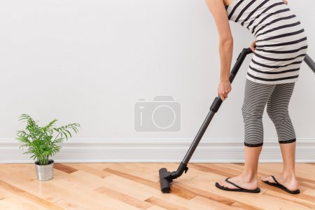 Woman vacuum cleaning the room