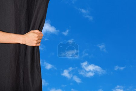 Hand opening a curtain with blue sky behind it