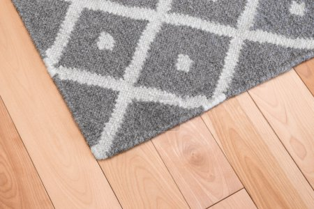 Photo for Contemporary gray wool rug on wooden floor. - Royalty Free Image