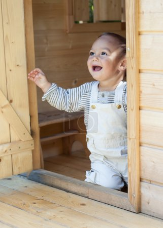 Child playing in garden or toy house