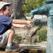 Child filling water bottle from a hydrant fountain...