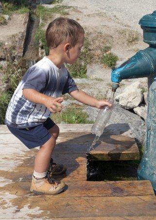 Photo pour Enfant remplissage bouteille d'eau d'une fontaine de bouche d'incendie. - image libre de droit