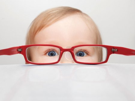 Photo for Picture of a child looking through red glasses - Royalty Free Image