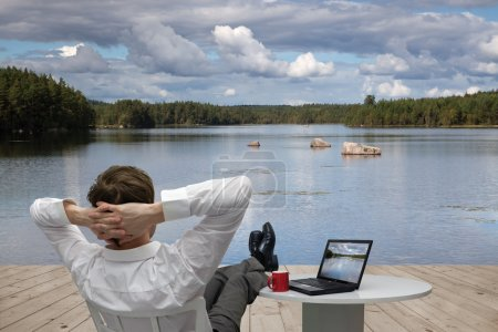 Photo for Businessman relaxing on the shore of Lake - Royalty Free Image