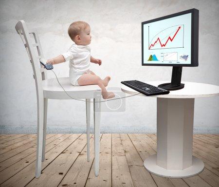 Photo pour Petit garçon assis à un bureau avec un ordinateur - image libre de droit