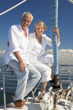 A happy senior couple sitting at the bow of a sail boat