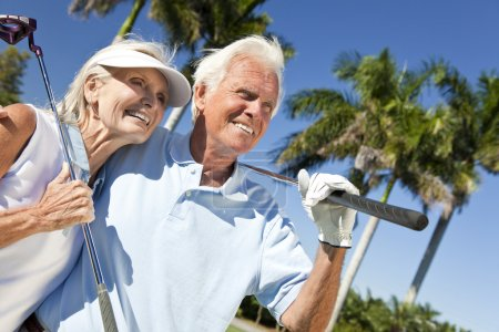 Photo for Happy senior man and woman couple together playing golf putting on a green together - Royalty Free Image