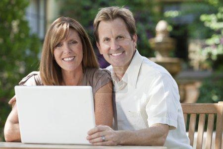Man & Woman Couple Using Laptop Computer In Garden