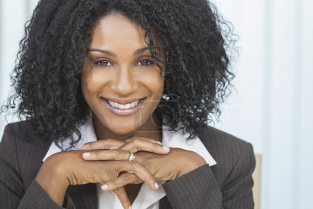 Foto de Portrait of a beautiful middle aged African American woman or businesswoman sitting relaxing & smiling - Imagen libre de derechos
