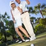 Постер, плакат: Happy Senior Couple Playing Golf Putting on Green