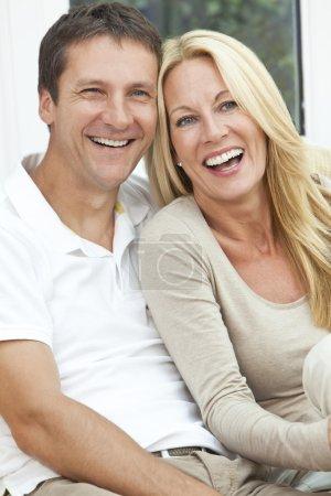 Foto de Toma de retrato de una atractiva, exitosa y feliz medio años hombre y mujer pareja en sus cuarentas, sentados juntos en casa en un sofá, sonriendo y riendo - Imagen libre de derechos