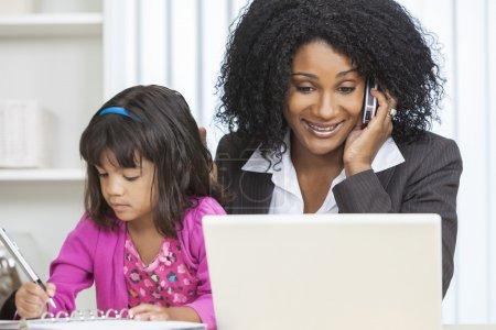 Foto de Hermosa mujer de mediana edad afroamericano o la empresaria que trabaja en su teléfono celular y la computadora portátil y el cuidado de su hija niña - Imagen libre de derechos