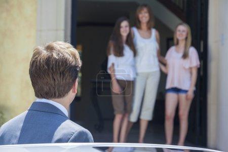 Photo pour Un père et son mari rentrent du travail pour voir sa famille de femmes et de filles - image libre de droit