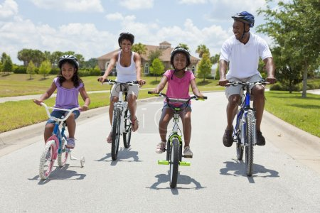 Photo for A Black African American family of two parents and two children, two girls, cycling together. - Royalty Free Image