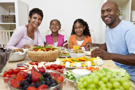 Photo for An attractive happy African American, smiling family of mother, father, two daughters eating salad and healthy food at a dining table. - Royalty Free Image