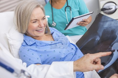 Photo for Happy senior woman patient recovering in hospital bed with male doctor and female nurse looking at hip replacement x-ray - Royalty Free Image
