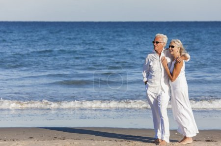 Photo for Happy senior man and woman couple together embracing by sea on a deserted tropical beach with bright clear blue sky - Royalty Free Image
