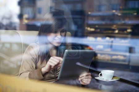Photo pour Jeune femme utilisant une tablette dans un café - image libre de droit
