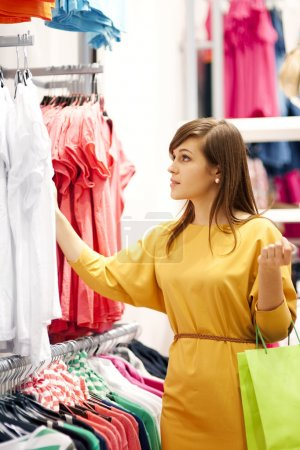 Photo for Young woman shopping for clothes - Royalty Free Image