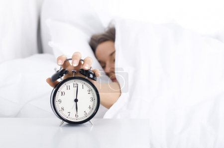 Photo for Woman turning off the alarm clock - Royalty Free Image