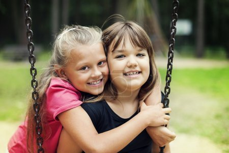 Photo for Best friends swinging in a park - Royalty Free Image