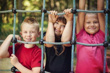 Photo for Happy children holding a net on playground - Royalty Free Image