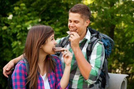 Photo for Young couple eating chocolate in forest - Royalty Free Image