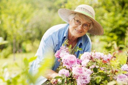 Photo pour Haute femme avec des fleurs dans le jardin - image libre de droit