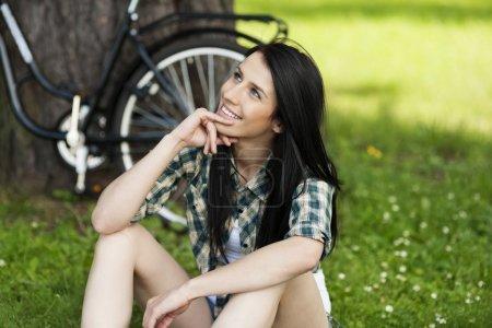 Photo pour Joyeux jeune femme au repos dans le parc - image libre de droit