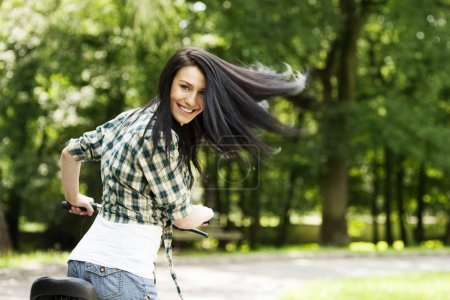 Photo for Happy young woman with bike in the park - Royalty Free Image