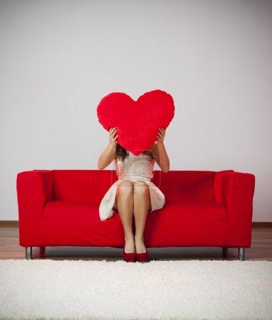 Woman holding heart shape pillow